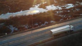 Coches y de la carga camiones semi cargados con las mercancías que conducen a lo largo de una carretera vacía almacen de video