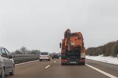 Coches y vehículo del propósito especial para la eliminación de residuos mojada en un autobahn, Alemania Foto de archivo