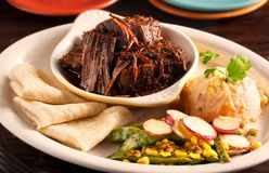 Cochinita pibil Entree with Side Orders and Tortillia Shells. At a Local Mexican Restaurant stock photo