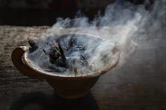 Cocido al vapor de la taza de la arcilla al vapor con las especias en la tabla de madera en calle Todavía fondo negro de la vida, Imagen de archivo