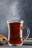 Cociendo la taza al vapor de té, aún vida en un fondo oscuro Imagen de archivo