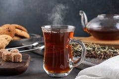 Cociendo la taza al vapor de té, aún vida en un fondo oscuro Imágenes de archivo libres de regalías