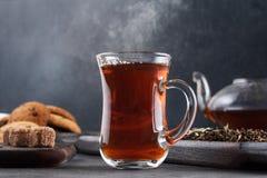 Cociendo la taza al vapor de té, aún vida en un fondo oscuro Fotos de archivo libres de regalías
