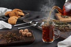 Cociendo la taza al vapor de té, aún vida en un fondo oscuro Imagenes de archivo
