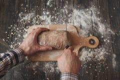 Cociendo y cocinando el fondo del concepto Las manos del pan del pan del corte del primer del panadero con el cuchillo en la tabl Foto de archivo