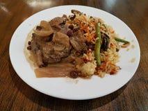 Cocina báltica, chuleta de la carne con las pasas y arroz con las verduras foto de archivo libre de regalías
