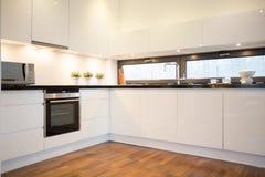 Cocina blanca con el piso de madera Fotografía de archivo libre de regalías
