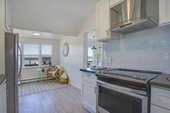 Cocina blanca con sala de estar llenada luz imagenes de archivo