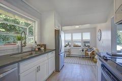 Cocina blanca con sala de estar llenada luz imagen de archivo libre de regalías