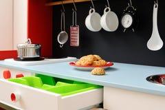 Cocina brillante del juguete con los cajones, los utensilios de la cocina y c hecha en casa Imagenes de archivo