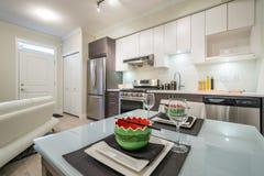 Cocina brillante moderna con una tabla de cena Foto de archivo