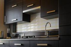 Cocina completamente cabida moderna contemporánea en marrón con los dispositivos superiores de espec. foto de archivo libre de regalías