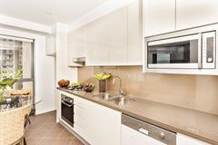 Cocina con las herramientas lujosas y las paredes blancas imagen de archivo