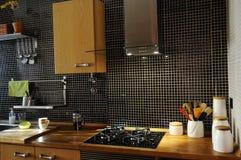 Cocina con las tejas negras y el contador de madera natural Fotos de archivo libres de regalías