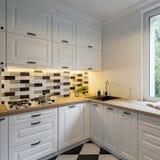 Cocina con los gabinetes y la pared de ladrillo clásicos imagen de archivo
