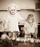 Cocina de dos pequeñas hermanas en casa fotos de archivo