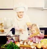 Cocina de dos pequeñas hermanas en casa fotografía de archivo