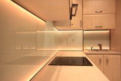 Cocina de lujo moderna con la iluminación amarilla del LED fotografía de archivo