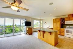 Cocina de oro de madera con el comedor, la TV y las porciones de ventanas al balcón Imagenes de archivo