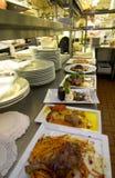 Cocina de trabajo del restaurante con la comida Imagen de archivo libre de regalías
