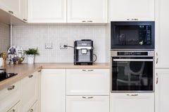 Cocina del diseño moderno con los dispositivos eléctricos y el worktop de madera Foto de archivo libre de regalías