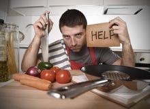 Cocina del hombre joven en casa en el delantal del cocinero desesperado en cocinar la tensión Foto de archivo