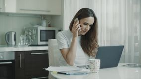 Cocina del tel?fono de la llamada de la mujer joven en casa Mujer de negocios que habla el tel?fono m?vil metrajes