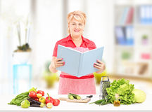Cocina femenina madura sonriente con el libro de los recipies que preparan sal Imágenes de archivo libres de regalías