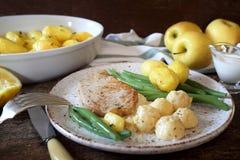 Cocina francesa: cerdo frito con la compota de manzanas, las habas verdes y las patatas Foto de archivo libre de regalías