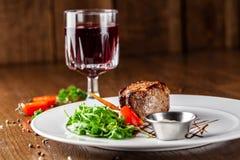 Cocina georgiana Filete de carne de vaca jugoso, filete de la ternera en una placa blanca con el cohete asado, verduras asadas a  imagenes de archivo