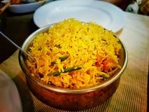 Cocina india del pulao del biryni del Handi del plato dulce del arroz en un cuenco en una tabla con las placas blancas imagen de archivo libre de regalías