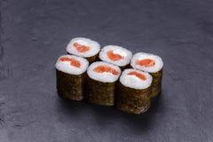 Cocina japonesa clásica, rollos de sushi con los salmones en sto negro Imagen de archivo