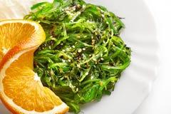 Cocina japonesa Ensalada de la alga marina con la naranja en la placa blanca Imagen de archivo