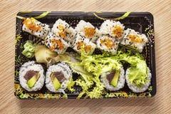 Cocina japonesa: Uramaki y Futomaki sabrosos sirvieron en la caja para llevar Imagen de archivo libre de regalías