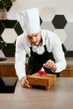 Cocina masculina de Decorating Dessert In del cocinero de pasteles fotografía de archivo