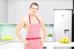 Cocina masculina descamisada con el delantal que presenta en una cocina Imagenes de archivo