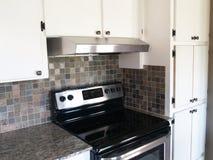 Cocina moderna con los gabinetes y la estufa blancos Foto de archivo