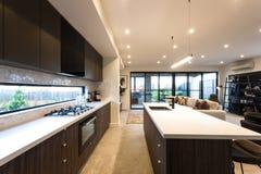 Cocina moderna iluminada con las luces de techo en el tiempo del día foto de archivo libre de regalías
