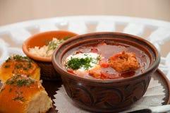 Cocina nacional ucraniana, borsch rojo con la carne y la crema agria en una bandeja con tocino, pampushkas del ajo y verdes Imagenes de archivo