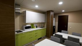 Cocina pequeña, moderna con los gabinetes verdes y dos tabels, comiendo la zona para los oficinistas Simple y pequeño, nuevo, ver almacen de video