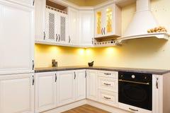Cocina vacía blanca con muebles blancos ligeros - luces calientes y madera agradable adornada fotografía de archivo