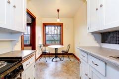 Cocina vieja blanca con la pequeña mesa de comedor. Imagen de archivo libre de regalías