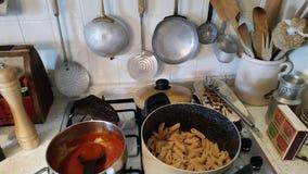 Cocina y cookware italianos con las pastas y la salsa foto de archivo