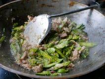 Cocinando el cerdo y las flores de trompeta indias Maridmai sofrió con goma tailandesa del chile en un wok en casa fotos de archivo libres de regalías