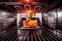 Cocinando el pollo en el horno en casa Fotografía de archivo libre de regalías