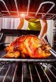 Cocinando el pollo en el horno en casa Foto de archivo