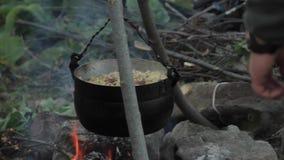 Cocinando en condiciones de campo, cacerola de ebullición en la hoguera almacen de metraje de vídeo