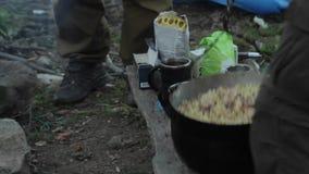 Cocinando en condiciones de campo, cacerola de ebullición en la hoguera metrajes