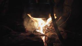 Cocinando en condiciones de campo en la noche, cacerola de ebullición en la hoguera almacen de metraje de vídeo