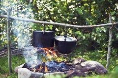 Cocinando en un viaje que camina, comiendo en las montañas, turismo El cocinar en la participación fotos de archivo libres de regalías